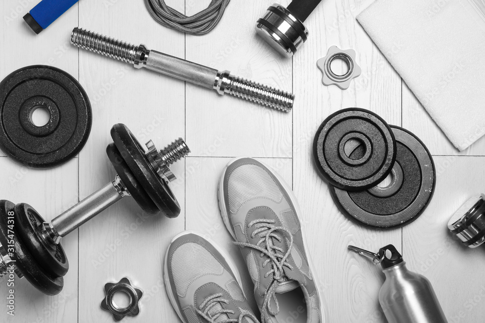 Fototapeta Gym equipment and shoes on wooden floor, flat lay