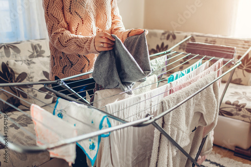 Canvastavla Woman folding gathering clean clothes from dryer after washing at home