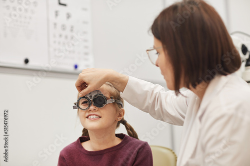 Fotografía Portrait of female optometrist setting up trial frame while checking eyesight of