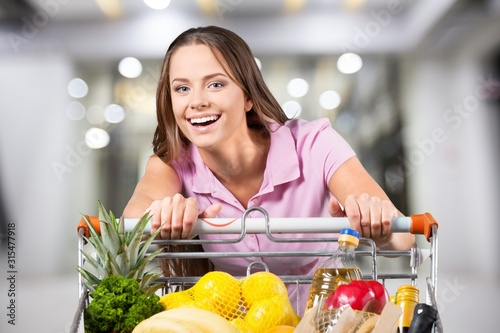 Woman with cart shopping in supermarket