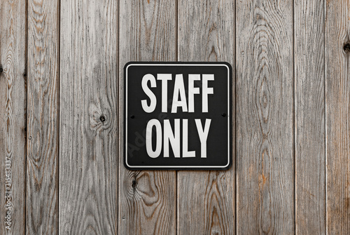 Black and white square STAFF ONLY sign attached to a wooden wall. Canvas Print