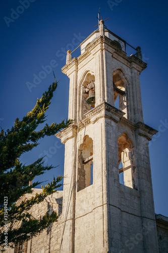The bell tower of the old church against the sky. Tapéta, Fotótapéta