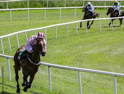 Fotografía  winning race horse and jockey in the lead position