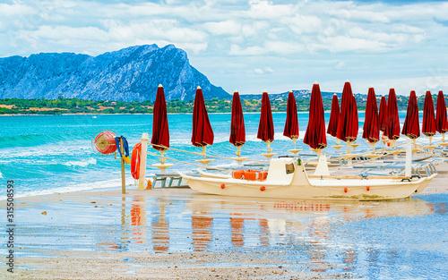 Landscape with umbrellas on La Cinta beach and Mediterranean Sea and Tavolara Island in Sardinia on Italy in summer Wallpaper Mural