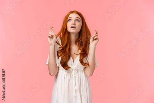 Hopeful and excited, dreamy cute redhead girl making wish on shooting star, look Wallpaper Mural