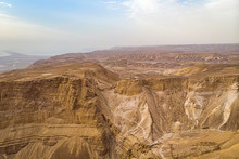 Geological Rock Formation In The Judean Desert, Israel. Natural Rock Canyons And Hills Shot At Skyscape Background From Air. Picturesque View To Sepia Rock Layers. Lifeless Earth Surface