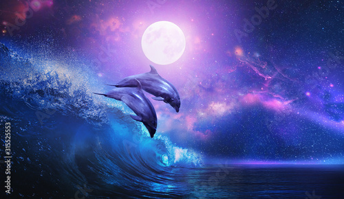 Fototapeta Night ocean with a pair of beautiful dolphins leaping from sea on surfing wave and full moon shining on tropical background obraz