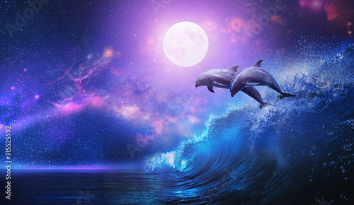 Night ocean with a pair of beautiful dolphins leaping from sea on surfing wave a Tableau sur Toile