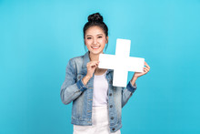 Happy Asian Woman Standing And Holding Plus Or Add Sign On Blue Background. Cute Asia Girl Smiling Wearing Casual Jeans Shirt And Showing Join Sign For Increse, Upgrade And More Benefit Concept