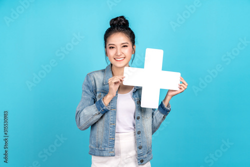 Happy asian woman standing and holding plus or add sign on blue background Canvas Print