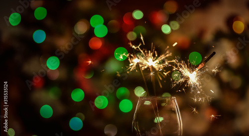 Foto Burning sparklers in a glass and bokeh orbs background