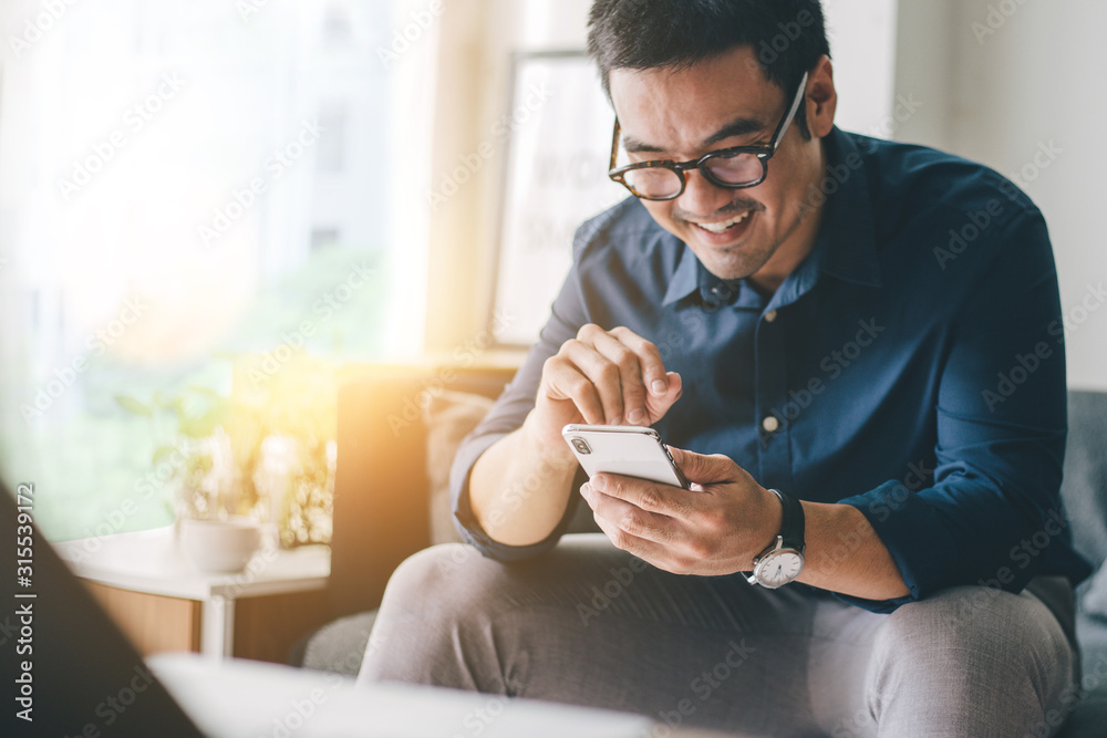 Fototapeta using cell phone.hand holding texting message on screen mobile chatting friend ,search internet information sitting on sofa in office.technology device contact communication connecting people concept