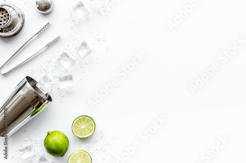 Bar background. Tools and ingredients for making cocktails. Shaker, lime, ice on white background top-down frame copy space