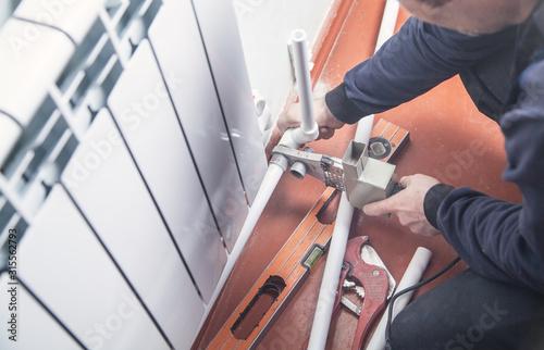 Worker connecting plastic pipe. Installing water heating radiator Wallpaper Mural