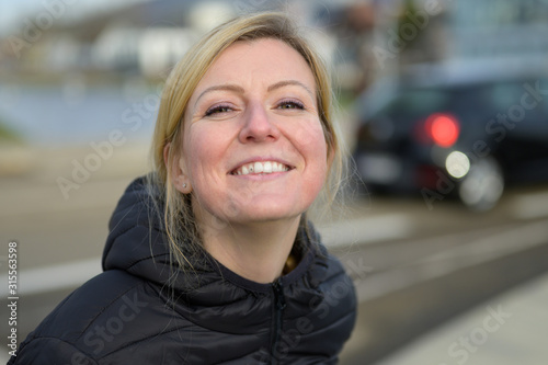 Foto Cute young blond woman with an impish grin