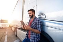 Professional Truck Driver Checking His Route On Tablet Computer And Standing By Long Vehicle. Transportation Service.