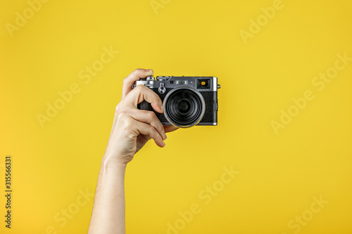 Obraz na plátně Camera held by one hand in front of a yellow background