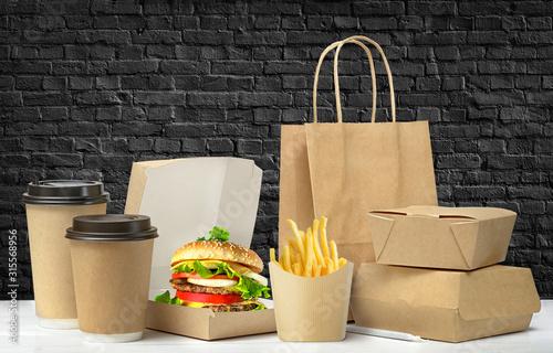 Fototapeta Fast food big lunch packaging set on black brick wall background. obraz
