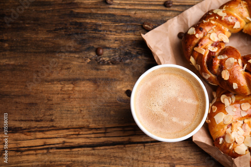 Fototapeta Delicious pastries and coffee on wooden table, flat lay. Space for text obraz