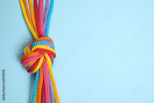 Fototapeta Top view of colorful ropes tied together on light blue background, space for text. Unity concept obraz