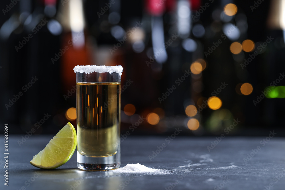 Fototapeta Mexican Tequila shot with lime and salt on bar counter. Space for text