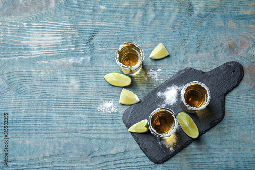 Mexican Tequila shots, lime slices and salt on blue wooden table, flat lay Fototapet