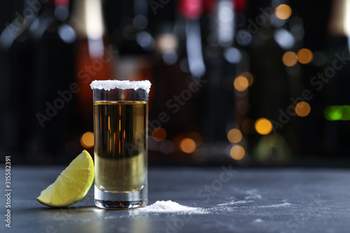 Fototapeta Mexican Tequila shot with lime and salt on bar counter. Space for text obraz