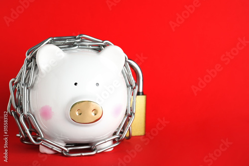 Fototapeta Piggy bank  with steel chain and padlock on red background, space for text. Money safety concept obraz