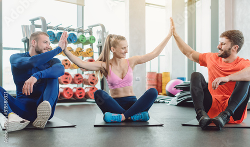 Obraz Group of fit friends in the gym giving a high five for motivation - fototapety do salonu