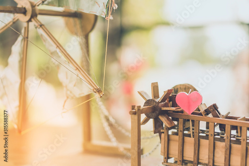 Photo Red heart shaped candle on a turbine baler model made of wooden on table