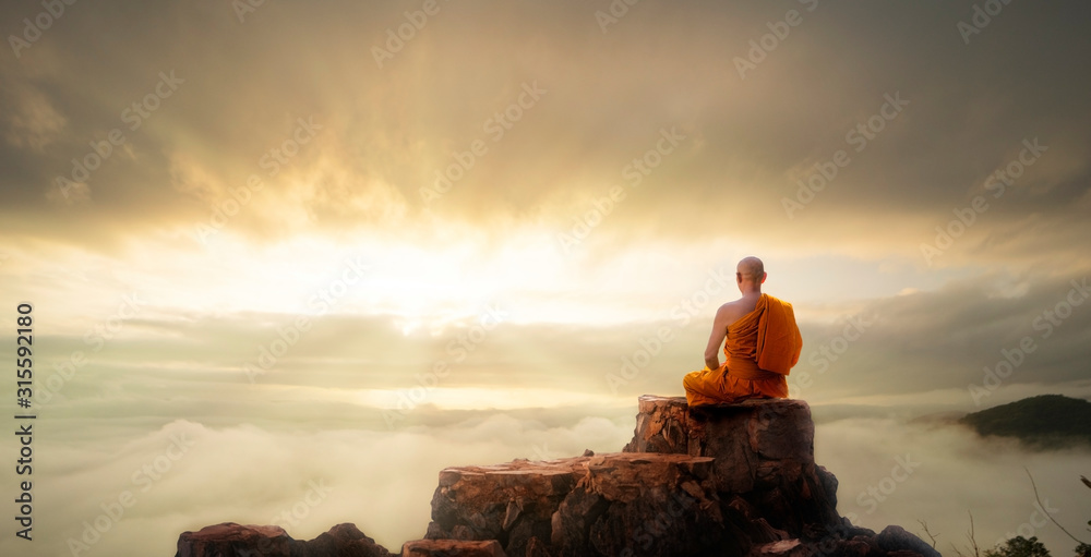 Fototapeta Buddhist monk in meditation at beautiful sunset or sunrise background on high mountain
