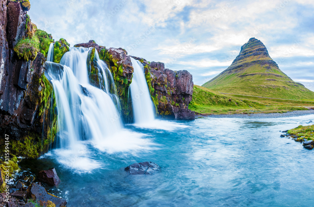 Fototapeta Beautiful natural magical scenery with a waterfall Kirkjufell near the volcano in Iceland. Exotic countries. Amazing places. Popular tourist atraction. (Meditation, antistress - concept).