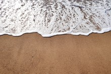 A Downward Shot Of A Foamy Waters Edge On Sand