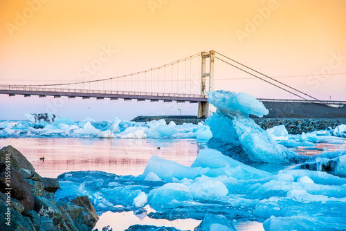 Iceberg parts float to the ocean under a bridge in the bay in the famous Jokulsarlon ice lagoon in Iceland Wallpaper Mural