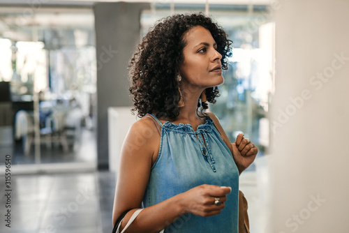 Fotografia  Young woman looking in a boutique window while out shopping