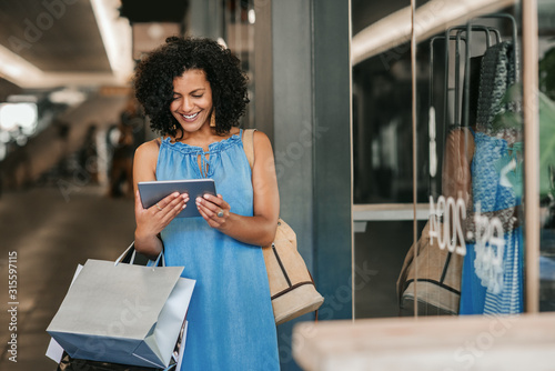 Tela  Young woman smiling and using a tablet while out shopping