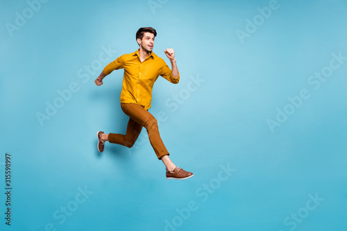 Fotografija Full length profile photo of funny excited guy jumping high running speed almost