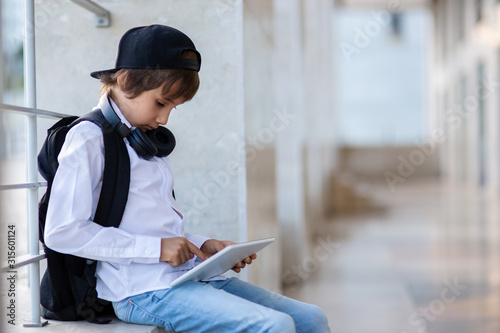 Photo Elementary schoolboy with backpack and tablet pc outside school