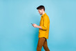 Profile side view portrait of his he nice attractive cheerful cheery guy using digital device walking free time isolated on bright vivid shine vibrant blue green turquoise color background