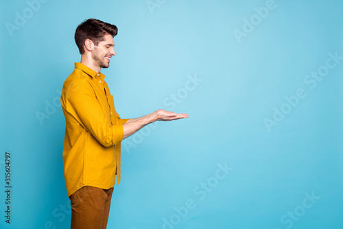 Photo of adoring man holding object with hands wearing yellow shirt trousers pan Canvas Print