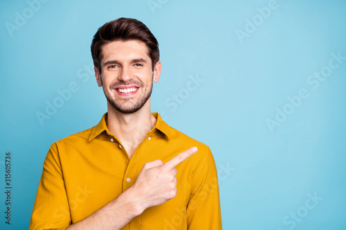 Photo of handsome cheerful attractive beaming man pointing at empty space with forefinger smiling toothily isolated over blue pastel color background