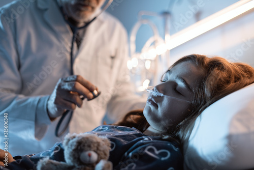 Doctor examining a child on the hospital bed at night Wallpaper Mural