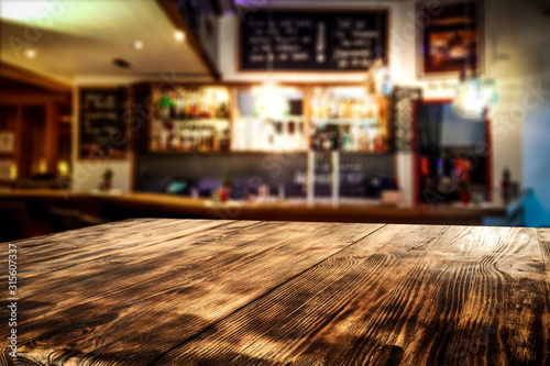 Obraz desk of free space for your decoration and blurred bar background.  - fototapety do salonu