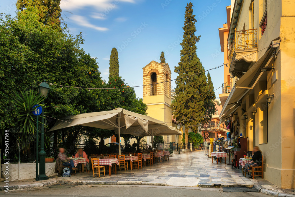 Old cozy street in Plaka district, cafes and restaurants in Athens, Greece