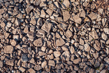 Abstract Background With Dry Uneven And Different Stones Lit By Sun Light. Texture