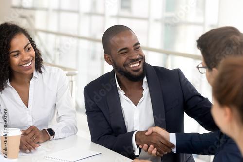 Photo Smiling black businessman handshake male partner at meeting
