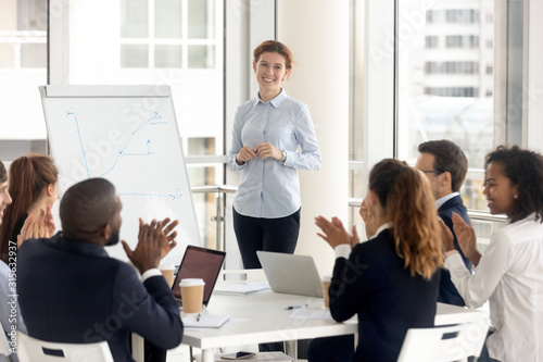 Photo Diverse employees applaud thanking coach for training