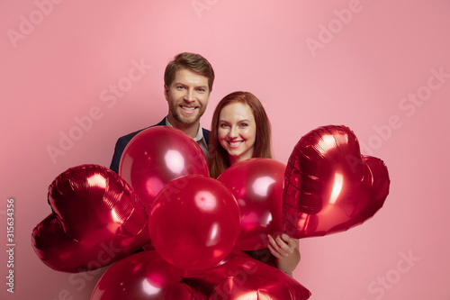 Fototapeta Happy holding balloons shaped hearts. Valentine's day celebration, happy caucasian couple on coral background. Concept of human emotions, facial expression, love, relations, romantic holidays. obraz