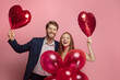 canvas print picture Happy holding balloons shaped hearts. Valentine's day celebration, happy caucasian couple on coral background. Concept of human emotions, facial expression, love, relations, romantic holidays.