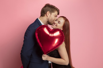 Fototapeta na wymiar Happy holding balloons shaped hearts. Valentine's day celebration, happy caucasian couple on coral background. Concept of human emotions, facial expression, love, relations, romantic holidays.